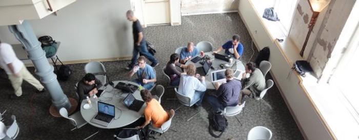 Сильно увеличенная и неинформативная фотография каких-то мальчиков с ноутбуками в обшарпанном зале